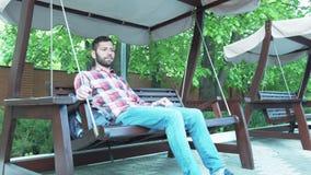 Um homem novo está balançando em um sofá-balanço de madeira O homem teve uma ruptura vídeos de arquivo