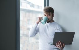 Um homem novo está com um portátil na janela e bebe o café de um copo Um empregado trabalha em uma ruptura Foto de Stock Royalty Free