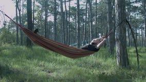 Um homem novo está dormindo em uma rede na floresta que o turista está descansando em uma rede vídeos de arquivo