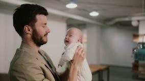 Um homem novo está guardando um bebê em seus braços e está falando, beijando o em um mordente Fundo do sótão vídeos de arquivo