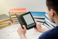Um homem novo está lendo um eBook no fundo do papel velho Fotos de Stock Royalty Free