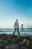 Um homem novo está na costa, e em fotografar a natureza com a câmera em um tripé foto de stock royalty free