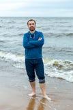 Um homem novo está no litoral Fotos de Stock Royalty Free