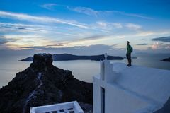 Um homem novo está no telhado branco de uma igreja na ilha romântica famosa de Santorini fotos de stock