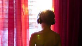 Um homem novo está perto da janela e põe sobre fones de ouvido para escutar a música Fundo borrado com o por do sol, adolescente vídeos de arquivo