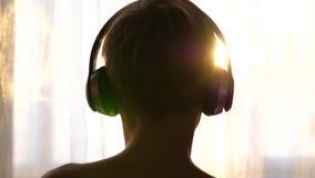 Um homem novo está perto da janela e põe sobre fones de ouvido para escutar a música Fundo borrado com o por do sol, adolescente video estoque