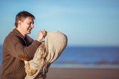 Um homem novo está puxando seu poncho dos wifes em sua cabeça Foto de Stock