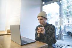 Um homem novo está sentando-se em um café acolhedor com uma xícara de café em suas mãos e está olhando-se um vídeo em um portátil Fotos de Stock