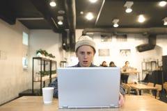 Um homem novo está trabalhando em um café e em olhares surpreendido na tela do portátil O estudante usa o Internet em um café aco Imagem de Stock