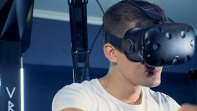 Um homem novo está vestindo auriculares da realidade virtual e está jogando o jogo da realidade 360 virtual filme