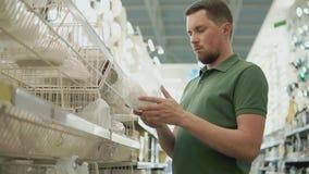 Um homem novo examina nas prateleiras uma lâmpada de rua em um shopping filme
