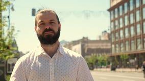 Um homem novo farpado está estando na rua retrato na cidade O homem é satisfeito com seus resultados Cidade grande Fisicamente co video estoque