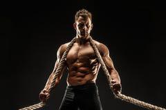 Um homem novo forte sexual considerável com o corpo muscular que guarda a corda fotografia de stock royalty free
