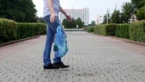 Um homem novo joga para fora um pacote do lixo no centro da cidade, litterbug filme