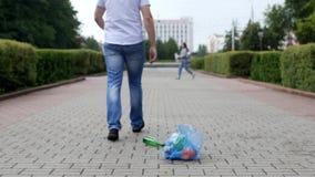 Um homem novo joga para fora um pacote do lixo no centro da cidade, litterbug vídeos de arquivo
