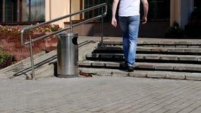 Um homem novo joga uma garrafa plástica perto da lata de lixo, desarrumada no centro da cidade vídeos de arquivo
