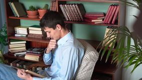 Um homem novo lê um livro ao se sentar na biblioteca de casa, um homem em uma camisa azul e as calças de brim guardam um livro e  vídeos de arquivo