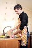 Um homem novo lava pratos Fotografia de Stock Royalty Free