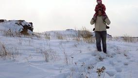 Um homem novo leva uma criança em seus braços em um monte que coberto de neve um blizzard começa vídeos de arquivo