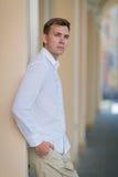 Um homem novo moderno em um fundo borrado da rua Um indivíduo sério na camisa e em culatras leves do verão Esfera 3d diferente Fotografia de Stock Royalty Free