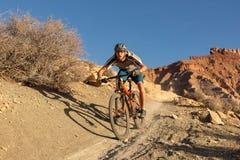 Um homem novo monta um Mountain bike abaixo da fuga de Jem no deserto de Utá do sul no dia de inverno ensolarado fotografia de stock