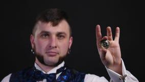 Um homem novo mostra truques com uma moeda em um fundo preto video estoque