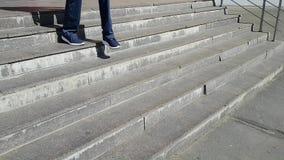 Um homem novo nas calças de brim abaixo das escadas da cidade O homem limps um pouco, ele tem uma inabilidade video estoque