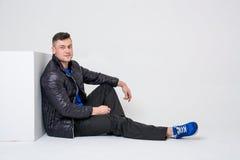 Um homem novo nas calças, em um revestimento e nas sapatilhas senta a inclinação em um cubo branco Imagens de Stock Royalty Free