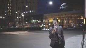 Um homem novo no ao ar livre com um telefone celular na noite Foto de Stock