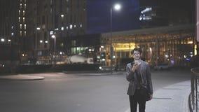 Um homem novo no ao ar livre com um telefone celular na noite Imagem de Stock