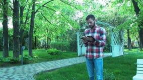 Um homem novo no parque que usa uma tabuleta é contratado no negócio Retrato de um estudante que inclina-se contra uma árvore ao  video estoque