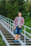 Um homem novo no short de manta de uma camisa e da sarja de Nimes está em um metal fotografia de stock