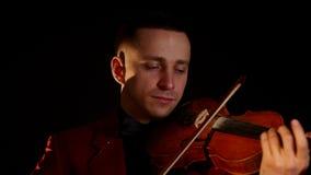 Um homem novo no terno vermelho joga o violino em um fundo preto video estoque
