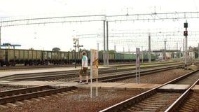 Um homem novo nos fones de ouvido cruza as trilhas railway e escuta a música, não ouve o trem de aproximação filme