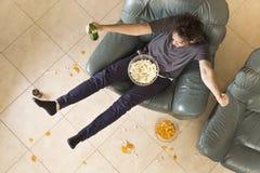 Um homem novo olha o fósforo na televisão ao relaxar fotografia de stock