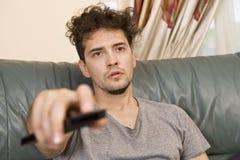 Um homem novo olha a televisão e muda os canais ao relaxar imagens de stock