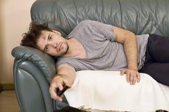 Um homem novo olha a televisão e muda os canais ao relaxar fotos de stock