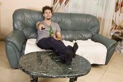 Um homem novo olha a televisão e muda os canais ao relaxar imagem de stock