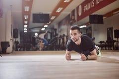 Um homem novo, olhando afastado, exercício da prancha, assoalho do gym, imagens de stock