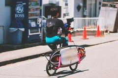 Um homem novo que biking para surfar no mar foto de stock royalty free