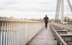 Um homem novo que corre em uma ponte Indivíduo que mantém seu corpo cabido pelo movimento imagens de stock royalty free