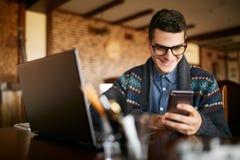 Um homem novo que datilografa um texto no smartphone moderno móvel Moderno que guarda um telefone moderno e que escreve uma mensa Fotografia de Stock Royalty Free