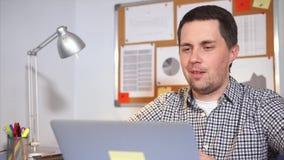 Um homem novo que fala a seus pais em um portátil usando um vídeo e o Internet vídeos de arquivo