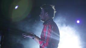 Um homem novo que fala a uma multidão em um concerto lighting Um homem caucasiano novo que fala a uma multidão em um concerto video estoque