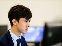 Um homem novo que focaliza em seu monitor do computador fotografia de stock