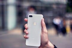Um homem novo que guarda um iphone branco no fundo de uma cidade borrada fotografia de stock