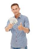 Um homem novo que guarda um punhado do dinheiro acima em seu punho Imagem de Stock