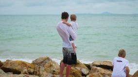 Um homem novo que guarda uma criança no litoral Família feliz video estoque