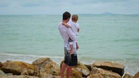 Um homem novo que guarda uma criança no litoral Família feliz vídeos de arquivo