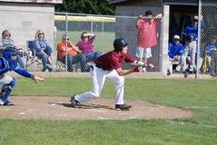 Um homem novo que joga o basebol da High School imagem de stock royalty free